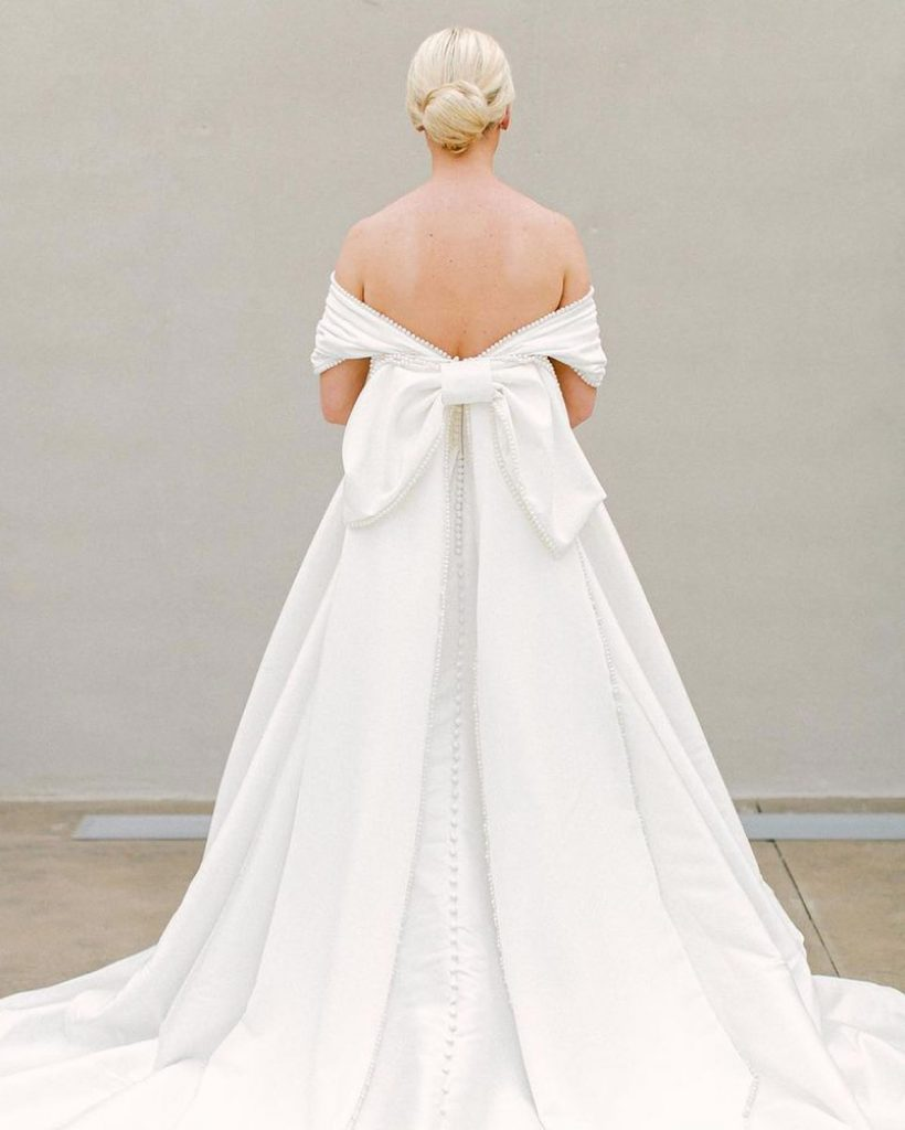 Take a bow for this custom bowed beauty created by avaribridal. This elegant, off-the-shoulder look has us smitten! Cheers to